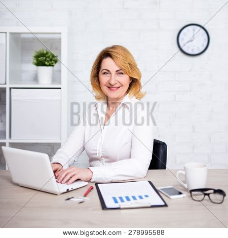 Portrait Of Mature Business Woman Working In Modern Office