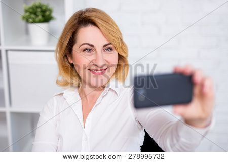 Portrait Of Cheerful Mature Business Woman Taking Selfie Photo With Smart Phone