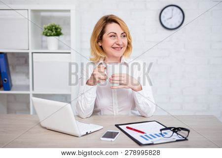 Cheerful Mature Business Woman Drinking Coffee In Modern Office