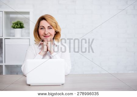 Mature Woman Sitting With Laptop In Modern Office Or Living Room - Copy Space Over White Brick Wall