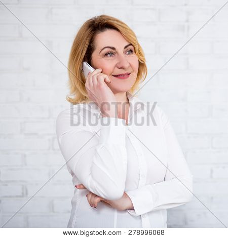 Portrait Of Cheerful Mature Business Woman Talking By Phone Over White Brick Wall