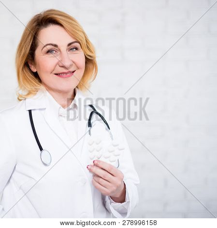 Health Care And Pharmacy Concept - Mature Female Doctor Or Nurse Holding Pills Over White Wall With