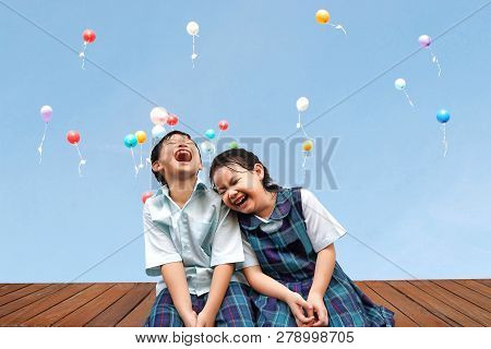Funny Asian Little Kids Brother And Sister Sitting On The Wooden Terrace With Colourful Balloons Bac