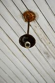 Old rusted light fixture on an white wood ceiling poster