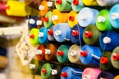 Colorful cones and spools of thread at an atelier.Tailoring, garment industry, designer workshop concept. embroidery thread spool.row of multicolored yarn rolls, sewing material.Workplace of tailor poster