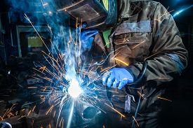 Man Welder In Welding Mask, Building Uniform And Blue Protective Gloves Welds Metal Car Muffler With