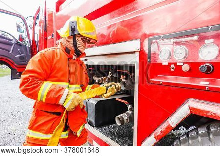 Firefighter Holding Water Hose Near The Truck With Equipment  At Fire Station