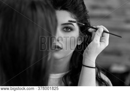 Black And White Portrait Of A Young Girl With Dark Long Hair, Whom The Stylist Does Makeup, Combing