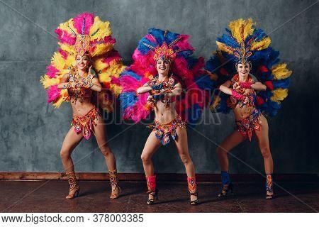 Three Woman Dancing In Brazilian Samba Carnival Costume With Colorful Feathers Plumage