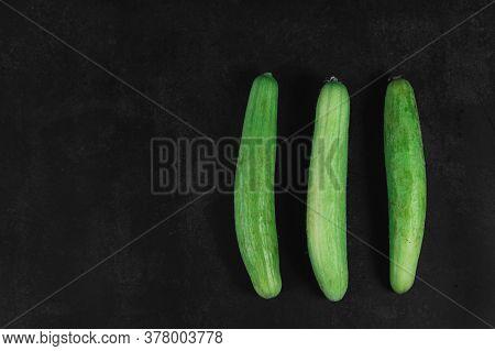 Three Organic Cucumbers On A Dark Background. Organic Eco Food. Healthy Diet. Freshly Picked Vegetab