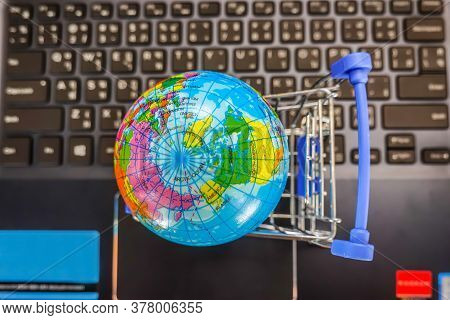 Top View Shopping Cart  With World Globe Balloon Map For Retail Business On Notebook. Image Use For
