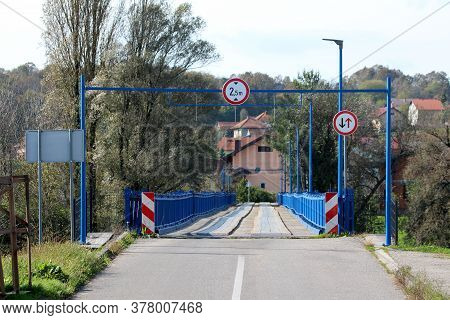 Entrance To Partially Renovated Wavey Old Wooden Bridge With New Blue Metal Frame On Each Side And S