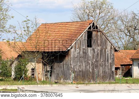 Old Abandoned Wooden Barn With Broken Dilapidated Wooden Boards And Destroyed Doors Next To Small Fa