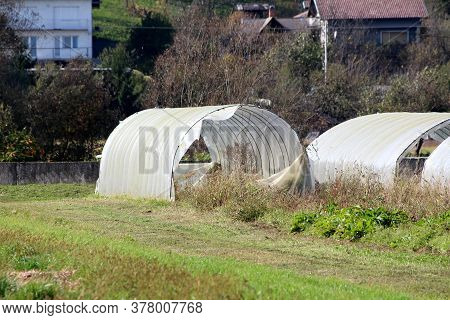 Old Open Dilapidated Large Garden Greenhouses Made Of Broken Metal Pipes Partially Covered With Crac