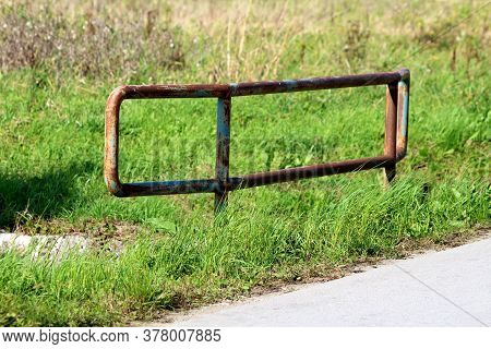 Strong Dilapidated Rusted Metal Protection Fence On Side Of Small Paved Bridge Over Water Canal Surr