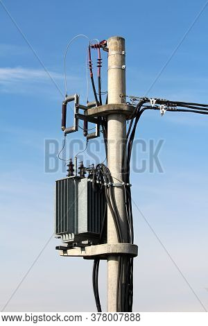 Strong Metal Electric Power Transformer With Grey Utility Box Mounted On High Concrete Utility Pole