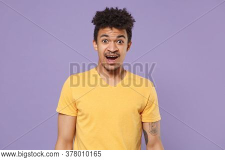 Shocked Perplexed Young African American Guy In Casual Yellow T-shirt Posing Isolated On Pastel Viol