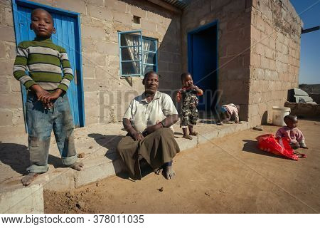 African granny and grandchildren group in a village in Botswana, sitting down in front of the blue door