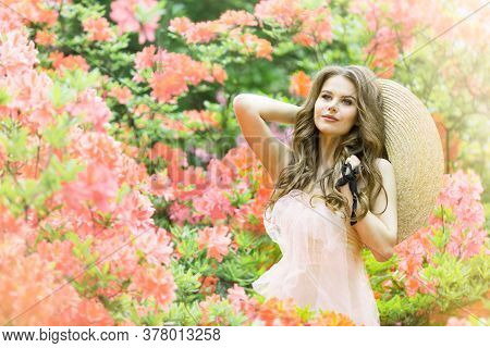 Fashion Model In Rhododendron Flowers, Beautiful Young Woman In Blooming Pink Garden, Outdoor Beauty
