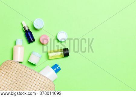 Top View Of Female Cosmetics Bag With Dropped Out Cosmetic Products On Green Background. Bodycare Co
