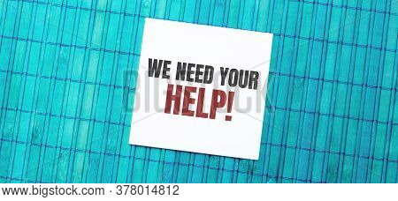 Blank Note Pad With We Need Your Help Text On Green Wooden Background