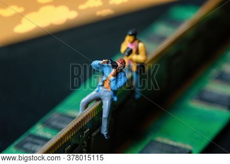 technology spy, photographer with camera walking on a lit keyboard