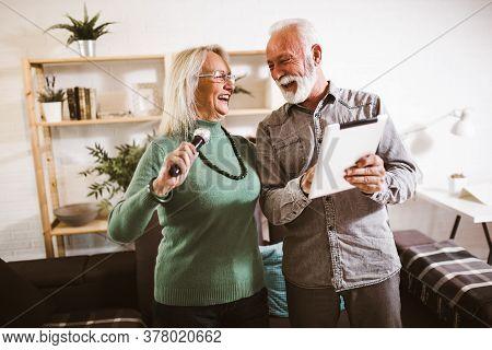 Senior Couple Singing Karaoke At Home, Having Fun.