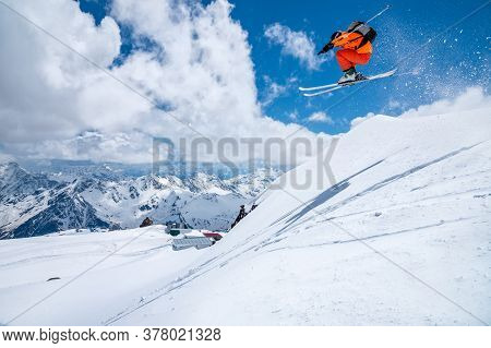 A Male Skier In An Orange Suit Flies In The Air After Jumping From A Snow Sweep High In The Caucasia