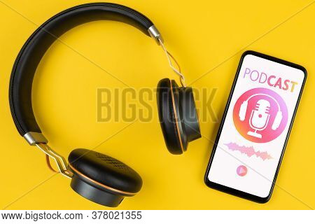 Podcasting Concept, Above View Of Headphones And Smartphone With Podcast Player Mockup On Yellow Bac