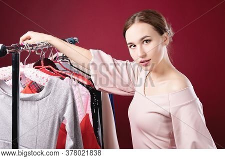 Serious Perplexed Standing Next To A Hanger For Things Holding One Hanger In Her Hand. The Concept O