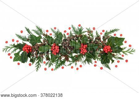 Winter greenery with holly & loose red berries, cedar cypress leaves, ivy & pine cones forming a festive display element for Christmas & New Year on white background. Flat lay, top view, copy space.