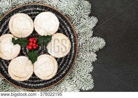 Traditional Christmas mince pies on a plate with winter berry holly & icing sugar dusting & snow covered fir on grey grunge  background. Festive food composition. Flat lay, top view, copy space.