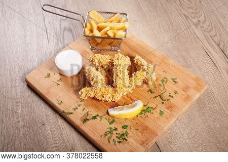 Corn Flakes Deep Fried Chicken Sticks And French Fries, Served On Wooden Board