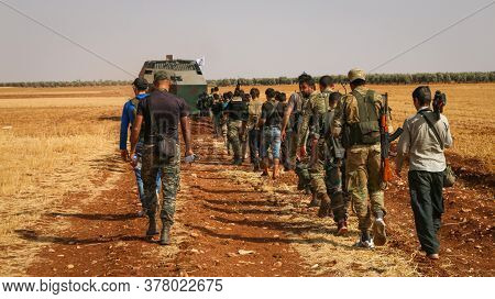 Aleppo, Syria 01 January 2017:\na Group Of Fighters Walks Behind A Military Mine Sweeper.