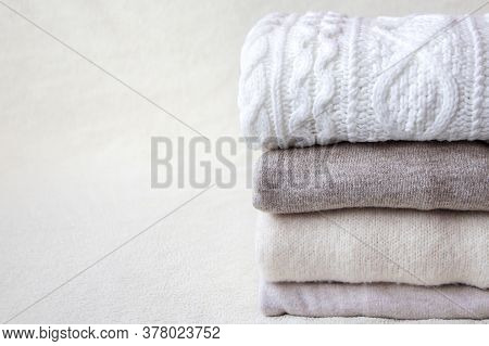 A Stack Of Beige And White Sweaters Lie On A Light Beige Soft Fabric Background. Folded Soft Warm Sw