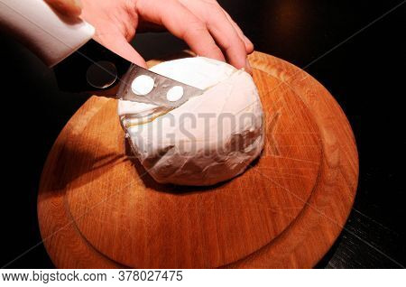 Cutting A Camembert In The Middle With A Cheese Knife On A Round Wooden Board