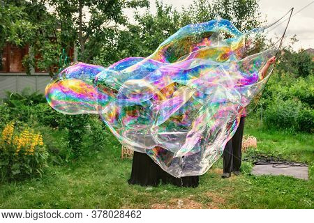 Close-up And Soft Focused Image Of A Huge Soap Bubble. Man Artist And Magician Shows A Performance W