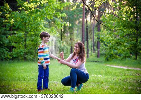 Young Woman Mother Applying Insect Repellent To Her Son Before Forest Hike Beautiful Summer Day Or E