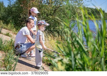 Father With Daughter And Son Sit On The Shore Of The Lake With Rods And Catch Fish. Concept Of Outdo