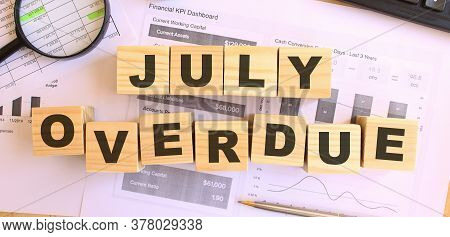 Wooden Cubes With Letters On The Table In The Office. Text July Overdue. Financial Concept.