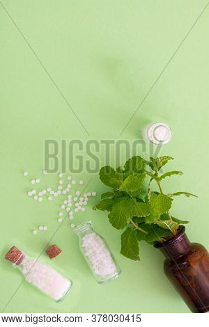 Homeopathy, Globules And Herbs On Green Background.