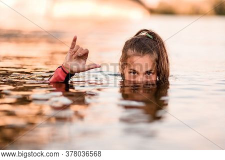 Head Of Young Woman Half Emerges From The Water And Her Hand Shows Gesture Of Greeting