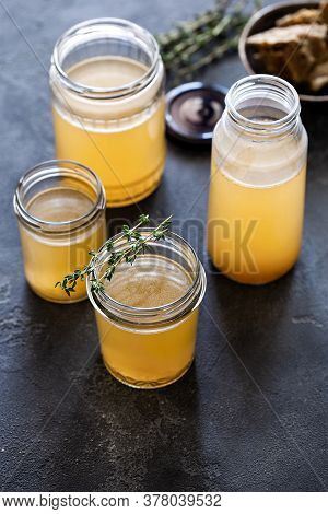 Glass Jar With Yellow Fresh Bone Broth On Dark Gray Background Top View. Healthy Low-calories Food I