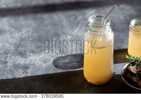 Fresh Vegetable Bone Broth In Glass Jar With Straw On Dark Gray Background. Healthy Dieting Food Are