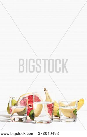 Fruit Banana, Pear, Kiwi And Grapefruit Distorted Through Glass Water On White Background. Modern Fo