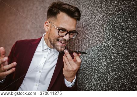 Young Business Man Using Voice Command Recorder On Smartphone.