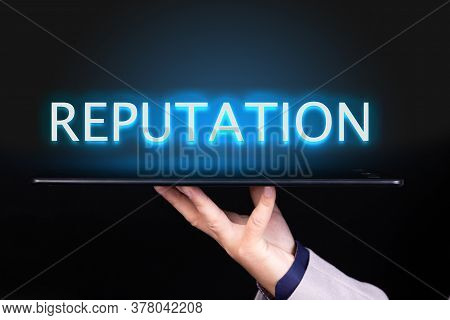 Man Hand Holds A Tablet Over Which A Neon Text Is Written, The Word Reputation. Business Concept.