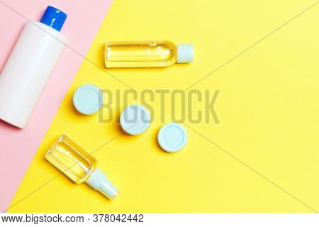 Group Of Plastic Bodycare Bottle Flat Lay Composition With Cosmetic Products On Yellow And Pink Back