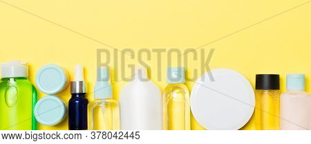 Set Of Cream And Cosmetics Bottles And Jars On Yellow Background. Bodycare Concept With Empty Space