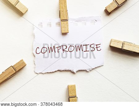 White Paper With Text Compromise With Clothespins On White Background